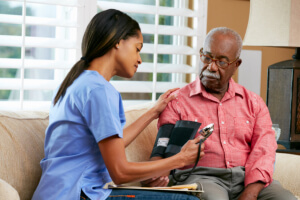 caregiver checking the blood pressure of the senior man