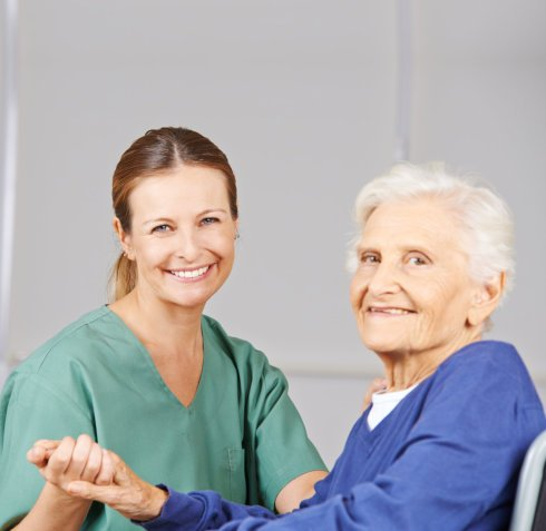 elderly woman holding her caregiver's hand
