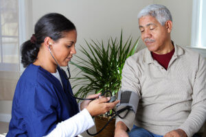 caregiver monitoring blood pressure of the old man